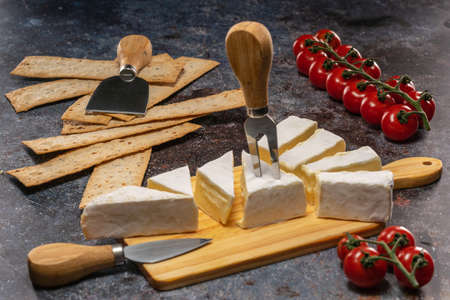 Cut Brie cheese lying on a cutting board next to tomatoes and flatbreads 免版税图像