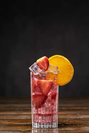 Pink cocktail with ice and strawberries, decorated with orange slice 免版税图像