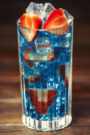 Blue cocktail with ice and strawberries. Close up. Selective focus
