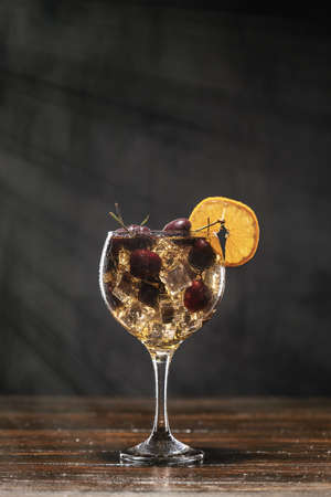 Yellow cocktail with cherry in a glass standing on a wooden table, decorated with a slice of orange