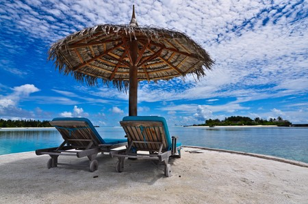 destinos: Beachchair con paraguas, Maldivas Foto de archivo