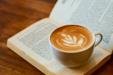 A cup of caffe latte place on a book or a novel Stock Photo