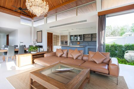 Luxury interior design in living room of pool villas. Airy and bright space with high raised ceiling and wooden dining table