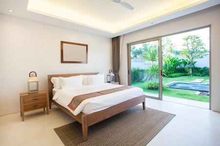 高級インテリアは居心地の良い王にプール ・ ヴィラの寝室のベッドを設計します。上げられた天井の高いベッドルーム 写真素材