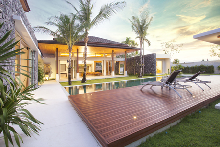 Interior and exterior design of pool villa which features living area, greenery garden, infinty swimming pool, wooden decking and sunbed surrounded by coconut tree