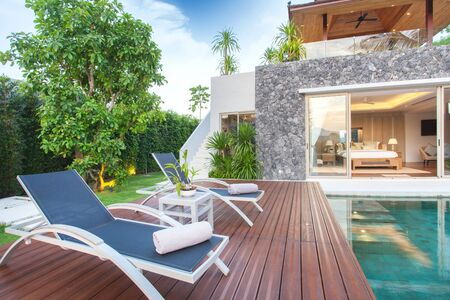 garage on house: Interior and exterior design of pool villa which features living area, greenery garden, infinty swimming pool, wooden decking and sunbed surrounded by coconut tree