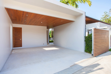 Interior and exterior design of white carport with wooden ceiling and wooden gated area