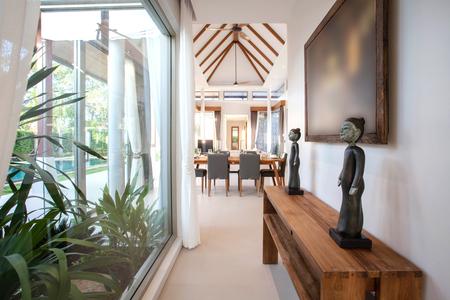 プール付きのヴィラのリビング ルームで豪華なインテリア デザイン。上げられた天井が高く、木製のダイニング テーブルと明るく広々 とした空間