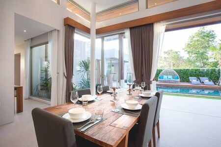 high ceiling: Luxury interior design in livingroom of pool villas. Airy and bright space with high raised ceiling and wooden dining table