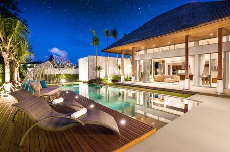 exterior and interior design of pool villa which features living area, greenery garden Фото со стока