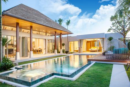 exterior and interior design of pool villa which features living area, greenery garden Foto de archivo