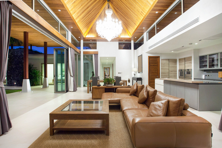 Luxury interior design in livingroom of pool villas. Airy and bright space with high raised ceiling and wooden dining table