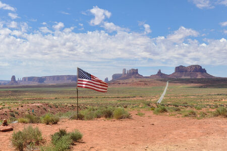 stratified: View of the Monument Valley with the American flag