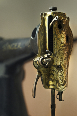 Old vintage retro broken sewing machine Singer. Yellow gold rusty floral pattern  ornament on front of sewing machine.