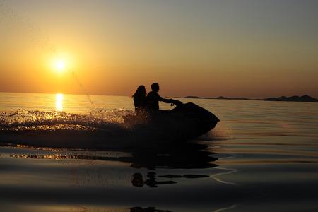 jetski: Couple on jetski in sunset Stock Photo