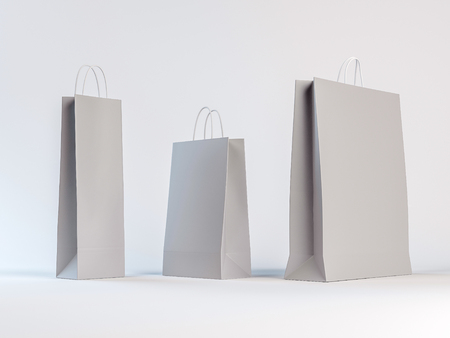Three different sizes of paper bags on a white background. Empty space with shadows allows easy placement of your design. Stock Photo