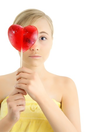 skintone: Young girl with a heart shaped candy in the hands isolated on a white background