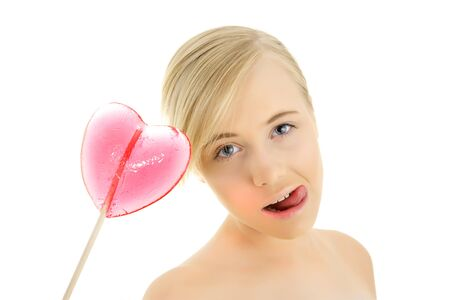 Young girl with a heart shaped candy in the hand isolated on a white background photo