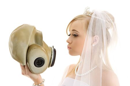 Young girl with a wedding dress and gasmask in the hand photo