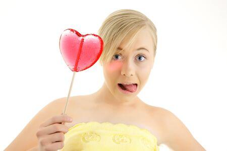 solter�a: Ni�a con un caramelo en forma de coraz�n en la mano aislado en un fondo blanco