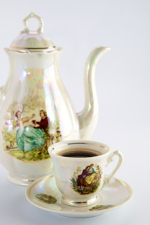 Beautiful old coffee pot and cup with a drawing photo