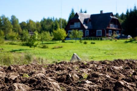 tierra fertil: tierra arable sobre fondo de granero y cielo de aldea  Foto de archivo