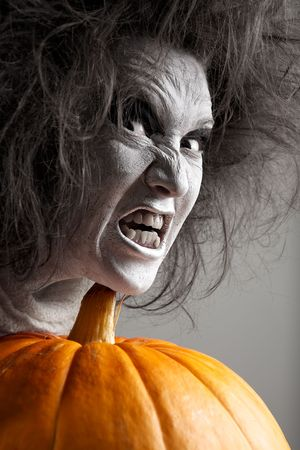demoniacal: Woman with a bleached face and pumpkin. Halloween theme.