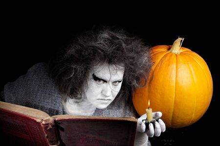 demoniacal: Witch with a magic book and pumpkin. Halloween theme. Stock Photo