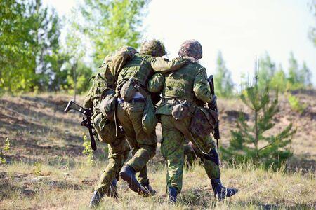 rifleman: Dos soldados del ej�rcito de la OTAN escoltaron al soldado herido Foto de archivo