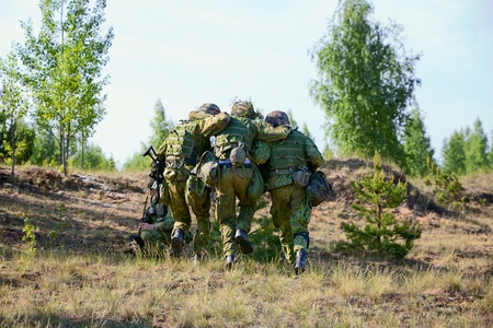 Two NATO Army soldiers escorted the wounded  soldier photo
