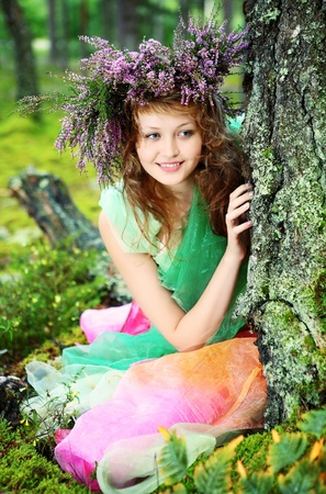 Young Fairy in the woods, leaning on a tree photo
