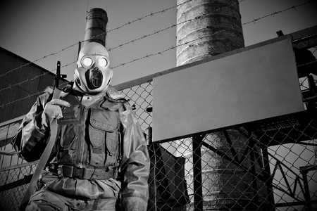 imminence: Russian solder with chemical hazard suit guarded secret object. With blank board for text. Monochrome.