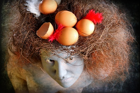 Woman with a painted face and a nest in hair photo