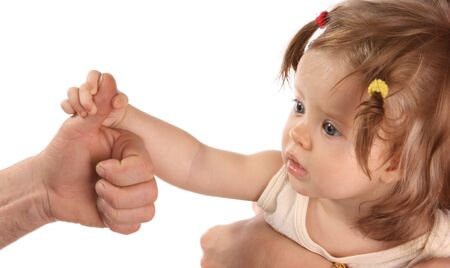 grasping: A baby holds on to the finger of hand.
