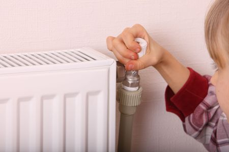 energy crisis: Girl try open thermostat. Energy crisis. Stock Photo