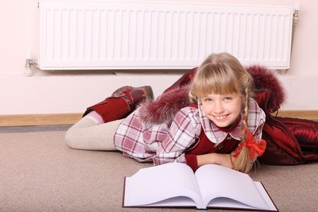 Girl lie near radiator with book. Cold crisis. photo