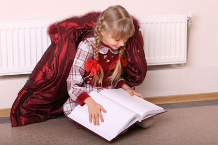 Girl lie near radiator with book. Cold crisis. Stock Photo - 4227560