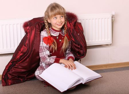 Girl lie near radiator with book. Cold crisis. Stock Photo - 4355135