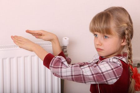 Girl warm ones hands near radiator.  Cold crisis. photo