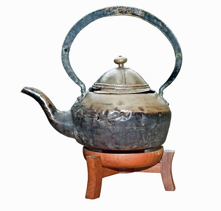 Ancient teapot on wood support.  Isolated. Stock Photo - 4878638
