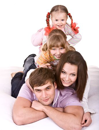 Happy family on white bed. Isolated. photo