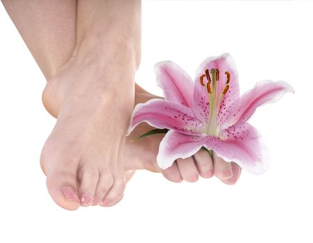Woman foot with flower lily. Isolated. photo