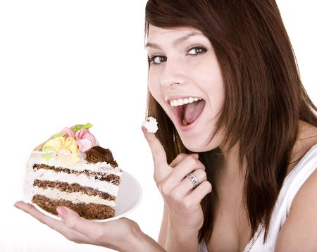 Girl eating piece of cake. Isolated. photo