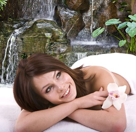 Girl in spa salon against waterfall. photo