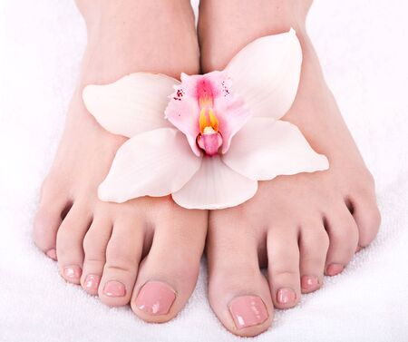 woman foot: Woman foot with flower lily. Isolated. Stock Photo