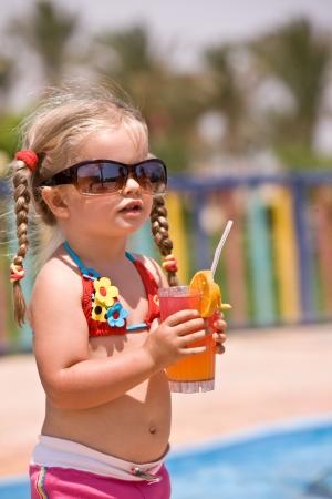 Child girl in sunglasses and red bikini drink orange juice. photo