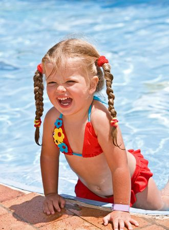 summer wear: Child girl in red bikini near blue swimming pool. Summer.