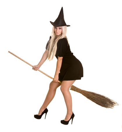 Halloween witch blond in black dress and hat on broom.Isolated. Stock Photo