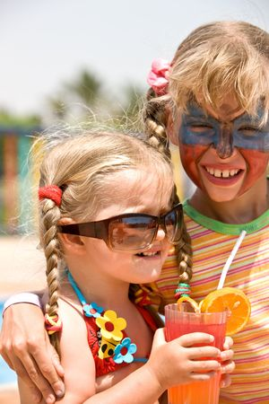 Two child girl with paint on face drink orange juice. photo
