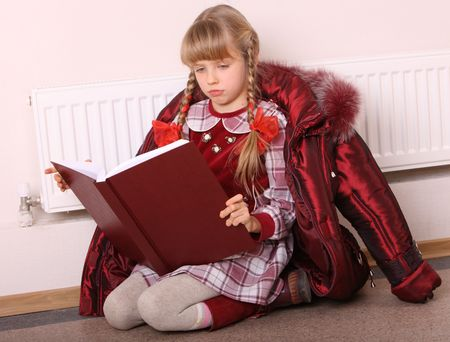 Girl lie near radiator with book. Cold crisis. Stock Photo - 5626619